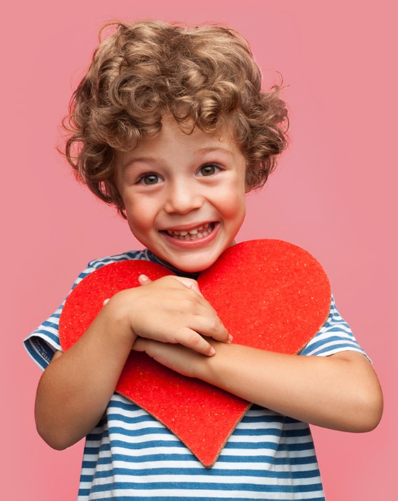 early treatment for a boy holding a big heart